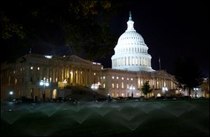 Sprinklers water the lawn outside the U.S. Capitol late Saturday night in Washington.