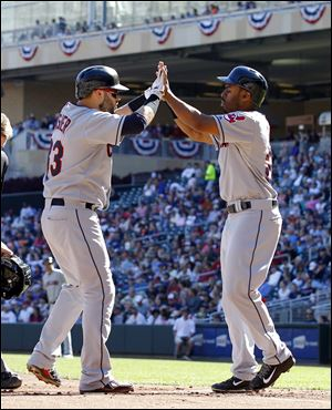 Cleveland's  Michael Bourn, right, welcomes Nick Swisher at home plate after they both scored on Swisher's home run off Twins pitcher Scott Diamond during the first inning Sunday in Minneapolis.
