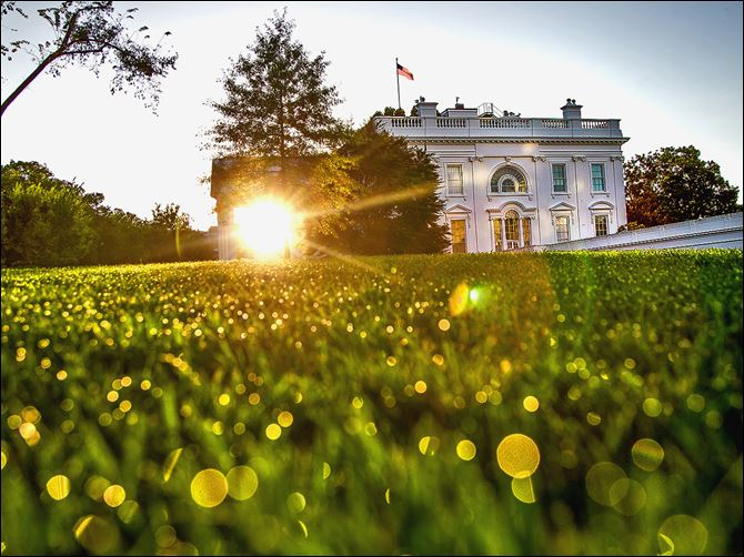 0001010102000000000 The sun rises behind the White House on Sunday morning as the debate continues over implementation of the nation's health-care law requiring insurance exchanges.