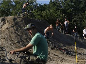 Alton Moran of Fostoria, center, rides down a mound as he and other riders work on the new Jermain BMX Bike Park.