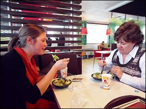 Aimie Zvosec of Chicago, left, and Dina Phillip of Naperville, Ill., dine on salads from McDonald's dollar menu in Oak Brook, Ill.