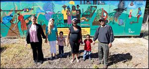 From left:  Yolanda Woodberry, Crystal Lanning, a resident of Moody Manor, Lanning's son Antonio Alvarez, 3, Bryonne Stenson, a resident of Moody Manor, Stenson's son Jeremiah Arnold, 4, and , Warren Woodberry, stand in front of a mural that the Woodberrys created at Moody Manor in a new garden.