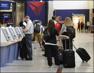 Delta Air Lines passengers line up to check luggage at Hartsfield-Jackson Atlanta International Airport in Atlanta. Delta customers now have the option to purchase an upgrade that includes a free checked bag, among other perks.