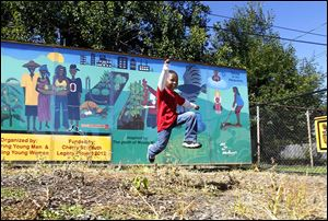 Jeremiah Arnold, 4, leaps past the mural that the Woodberrys created at Moody Manor in a new garden. Part of the mural has an image of Keondra Hooks, 1, who was killed at the apartment complex in August, 2012.