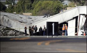 Airport officials and investigators stand near a collapsed hangar at the site of a plane crash in Santa Monica, Calif.