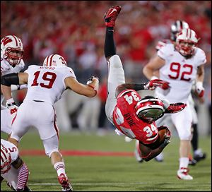 Ohio State tailback Carlos Hyde goes flying past Wisconsin's Leo Musso in Saturday's game. Hyde had 85 yards on 17 carries. The No. 4 Buckeyes play Saturday at No. 16 Northwestern.