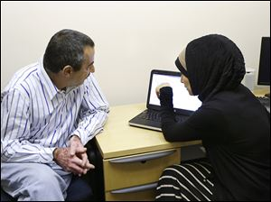 ACCESS Community Health and Research Center Navigator Nancy Berry, right, looks over an Affordable Care Act cost calculator with Hussein Daoud at the agency's center in Dearborn, Mich.