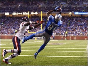 Detroit Lions wide receiver Calvin Johnson (81), defended by Chicago Bears cornerback Charles Tillman (33),  catches a two-yard touchdown from quarterback Matthew Stafford.
