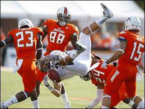 "Bowling Green's Jerry ""Boo Boo"" Gates (24) slams Akron's L.T. Smith on Saturday. The Falcons are stingy about giving up passing yards but have no interceptions."