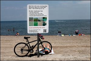 A sign alerts swimmers to the danger of algae this summer.