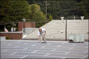 Mike Easterwood checks one of the solar panels installed on the roof of  his 1947-era building in Decatur,Ga.  Easterwood paid about $320,000 to install nearly 400 solar panels on top of his self-storage business near Atlanta.
