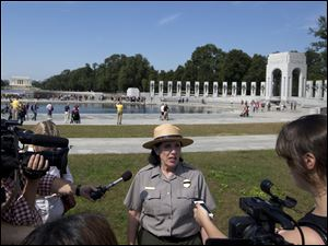 National Park Service spokeswoman Carol Johnson speaks to reporters at the National World War II Memorial in Washington, Tuesday as a group of veterans walked past barriers at the closed World War II memorial with help from members of Congress.