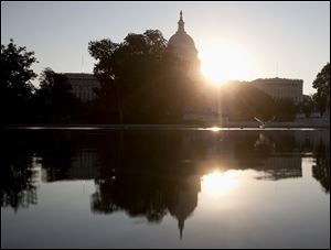 The sun rises behind the Capitol in Washington, today as the political stare-down on Capitol Hill shows no signs of easing