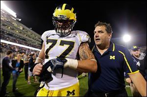 Michigan head coach Brady Hoke, right, talks with offensive linesman Taylor Lewan (77) after a win against Connecticut.