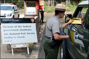 U.S. Park Ranger  Heidi Schlichting informs visitors of the closure of Yosemite National Park in California. President Obama brought top lawmakers from both parties to the White House but told them he would negotiate only after they fund the government and raise the debt limit without preconditions.