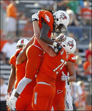 Clay Rolf hoists Bowling Green State University running back Travis Greene after Greene scored a fourth-quarter touchdown against Akron last Saturday. Rolf entered the game in the second quarter after an injury to team­mate Ja­cob Ben­nett.