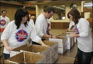 BIZ unitedway04p   Fifth Third employees Lauren Whetsel (cq), of Toledo, left, Ben Robie (cq), also of Toledo, and Amy Tyson, of Bowling Green add sweets to boxes.   Northwest Ohio Fifth Third Bank employees kick off their United Way campaign with a Day of Caring-helping Heroes in Action, a local military support group, to assemble care packages that will be sent to troops serving overseas-in Toledo, Ohio on October 3, 2013. A dozen volunteers work with the organization to package personal hygiene, snack foods, and magazines for the troops. Next month another group of Fifth Third employees will help the group as they assemble packages on the first Thursday of November.    The Blade/Jetta Fraser