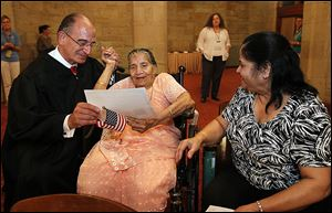 U.S. District Court Judge Jack Zouhary, left, presents Shardaben Chimanlal Vyas, 86, with her citizenship papers during the ceremony Thursday in Toledo. At right is her daughter-in-law, Anila Vyas. The elder Ms. Vyas lives with her son, Mahendra, and his family. She is a native of India.