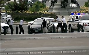 This image from video provided by Alhurra Television shows police with guns drawn surrounding a black Infiniti near the U.S. Capitol in Washington. A woman with a young child inside tried to ram through a White House barricade, then led police on a chase toward the Capitol, where police shot and killed her, witnesses and officials said.