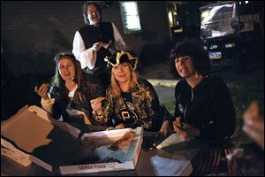 From left, Cleveland residents Jessica and Marco Bruno, Lisa Altschuler, and Wendy Robinson laugh as they talk and eat pizza while dressed as pirates. They visited Put-in-Bay in late September to celebrate Ms. Altschuler's upcoming birthday.