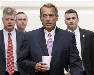House Speaker John Boehner of Ohio walks to a Republican strategy session on Capitol Hill in Washington today.