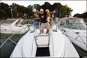 Donnie Jenei and Vicki Price of Stow, Ohio, dance on the bow of Mr. Jenei's boat as they celebrate a friend's bachelorette party. Mr. Jenei has been coming to Put-in-Bay for more than 30 years.