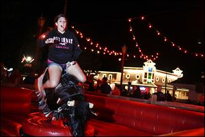 Jenica Reynolds of Erie, Pa., yells while riding a mechanical bull outside a tavern at Put-in-Bay, Ohio, on South Bass Island. Every year, thousands of visitors trek to the resort island for drinking, boating, and bar hopping.