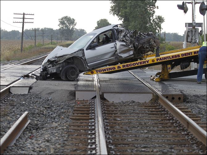 Workers from Reinhart Auto Body load a car onto a flatbed truck after it collided with a train at the CSX railroad tracks on U.S. 6 in Bradner, Ohio.