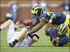 University of Michigan players Jarrod Wilson (22) and Courtney Avery (11) knock the ball from University of Minnesota quarterback Mitch Leidner (7) and out of bounds during the second quarter.