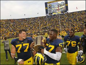 University of Michigan football players Taylor Lewan (77) and Frank Clark (57) carry the Little Brown Jug after the Wolverines defeated the University of Minnesota 42-13.