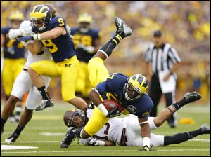 University of Michigan player Devin Funchess (87) dives for a first down.
