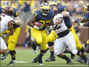 University of Michigan player Derrick Green (27) finds a hole during the third quarter.