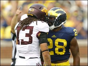 Michigan player Fitzgerald Toussaint (28) and Minnesota player Derrick Wells (13) jaw at each other during the third quarter.