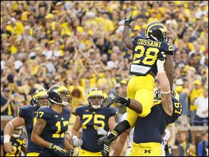 Michigan player Kyle Kalis (67) hoists running back Fitzgerald Toussaint (28) into the air after Toussaint scored against Minnesota