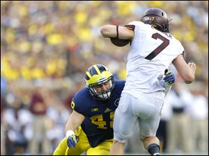 Michigan player Desmond Morgan (48) tackles Minnesota quarterback Mitch Leidner (7) during the fourth quarter.
