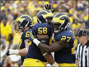 University of Michigan player Derrick Green (27) celebrates his touchdown with teammate Chris Bryant (58) during the third quarter.