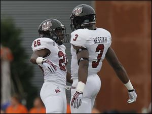 UMass players #26, Quayshun Smith and #3, Kassan Messiah celebrate a fumble recovery in the first period.