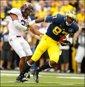 University of Michigan player Devin Funchess (87) breaks away from University of Minnesota player Martez Sabazz for a touchdown during the second quarter.