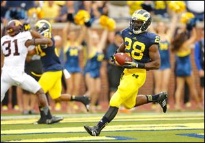 University of Michigan running back Fitzgerald Toussaint (28) scores a touchdown against University of Minnesota during the first quarter.