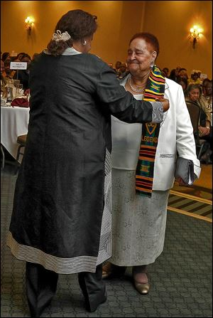 Helen Cooks places a scarf of honor around Lola Glover of the Coalition for Quality Education during the Legends Luncheon.