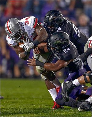 OSU's Carlos Hyde, who had 168 yards rushing, is tackled by Northwestern's Dean Lowry, top, and Ibraheim Campbell.