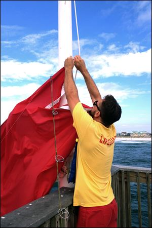 A lifeguard hangs a red flag indicating dangerous surf conditions at Pensacola Beach, Fla.