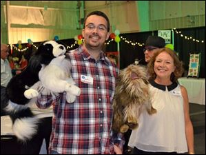 Justin Dowling and Linda Meeks hold up their stuffed four-legged teammates for the