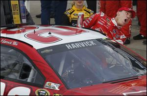 Driver Kevin Harvick climbs out of his race car in victory lane after winning the  NASCAR Sprint Cup series race Sunday at Kansas Speedway in Kansas City, Kan.