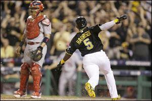 Pittsburgh Pirates pinch-runner Josh Harrison scores from second on a Pedro Alvarez single in the eighth innings as Cardinals catcher Yadier Molina awaits a possible throw.