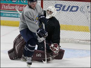 Walleyes Tyler Pilmore and goalie Brooks Ostergard.