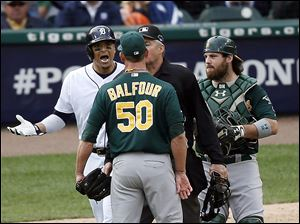 Home plate umpire Gary Darling, second from right, steps between Detroit Tigers designated hitter Victor Martinez, left, and Oakland Athletics relief pitcher Grant Balfour (50) during the ninth inning of Game 3 in Detroit.