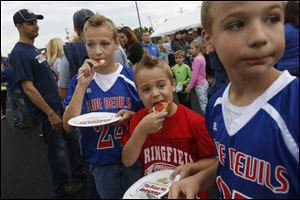 Brothers Joshua, 11, left, Garren, 7, center, and Welden Hannum, 10, enjoy pizza during a kick-off event last week to support a 2.9-mill levy on the November ballot for Springfield Local Schools.