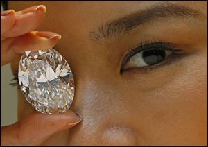 A 118.28-carat white diamond is displayed by a model at a press preview at Sotheby's auction house in Hong Kong.