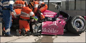 Safety team members work to remove Dario Franchitti from his car after a crash during the second IndyCar Grand Prix of Houston auto race, Sunday in Houston.